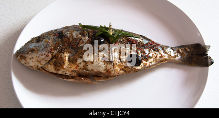 Gilthead seabream nicely marinated waiting on a plate ready for barbecue - Stock Photo
