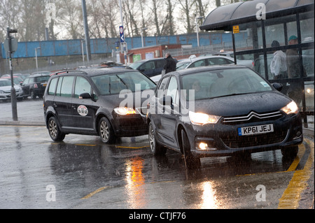 Taxi waiting for a car to move away from a taxi rank on a rainy day outside a railway station in England. - Stock Photo