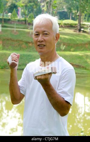 Senior man using dumbells on outdoor - Stock Photo