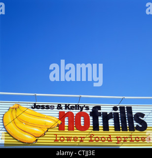 Jess & Kelly's No Frills sign on the exterior of the supermarket against a blue sky Ontario Canada - Stock Photo
