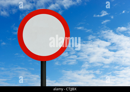 Red round road sign and blue sky - Stock Photo