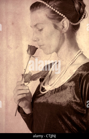 an elegant woman smelling a rose - Stock Photo