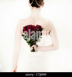 a woman in a white dress holding a bouquet of roses behind her back - Stock Photo