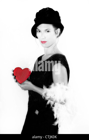a woman in an elegant black dress holding a red heart - Stock Photo