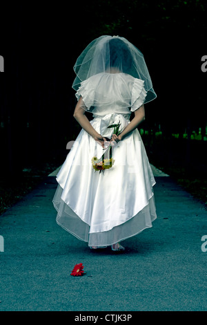 a woman in a wedding dress is walking through a dark alley - Stock Photo