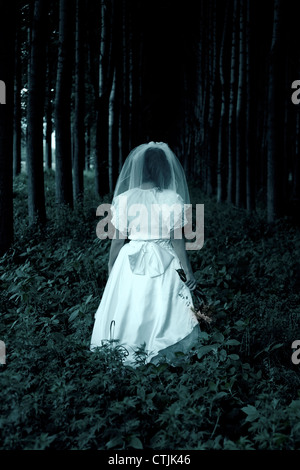 a woman in a wedding dress is walking through a forest - Stock Photo