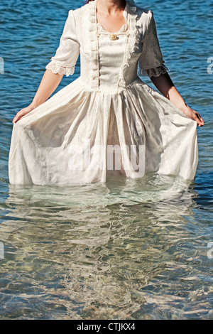 a woman in a white, Victorian dress standing in the water