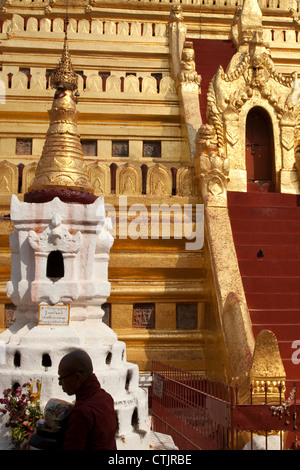 A monk walks past Shwezigon Pagoda (Paya) - a Buddhist temple located in Nyaung U, Myanmar (Burma). - Stock Photo