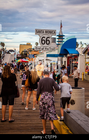 The end of Route 66 on the Santa Monica pier in California with tourists taking photos - Stock Photo