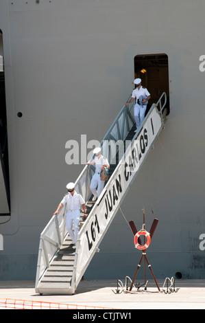 Spanish naval officers walking the gangplank of L61 Juan Carlos 1a Spanish warship al;ongside in Cartagena Spain - Stock Photo