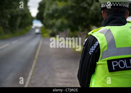 Traffic policeman on speed patrol check duties;  Police Traffic Officer, policing radar gun in North Yorkshire Dales - Stock Photo