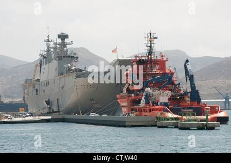 Bow to bow L61 Juan Carlos 1 and the tug Clara Campoamor in Cartagena Harbour Spain - Stock Photo