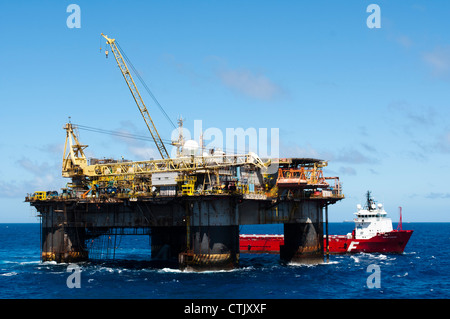 Oil Rig PXX from Petrobras, with supply vessel along side during transfer operations with cranes. - Stock Photo
