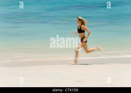 A Woman Tourist Runs Along The Beach On A Tropical Island; Koh Lanta,Thailand - Stock Photo