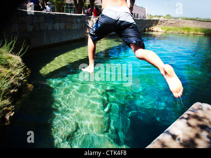 Twelve year old boy jumping into deep blue water at The Blue Hole, Santa Rosa, New Mexico. - Stock Photo