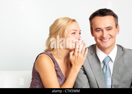 Cheerful woman whispering something funny in her husband's ear - Stock Photo