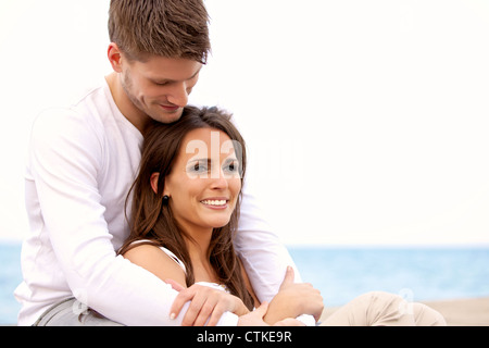 Portrait of an attractive couple hanging out by the sea against a bright background - Stock Photo