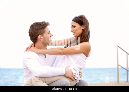 Portrait of a sweet couple looking at each other enjoying their time on a beach - Stock Photo