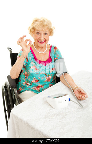Disabled senior woman in wheelchair taking her own blood pressure at home and giving the okay sign. White background. - Stock Photo