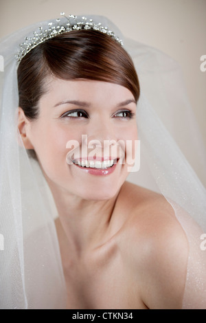 A young bride wearing a tiara and veil, looking to the side - Stock Photo