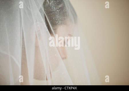 A young bride wearing a tiara and veil, looking down - Stock Photo