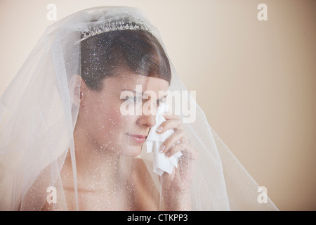 A young bride wiping tears from her face with a tissue - Stock Photo