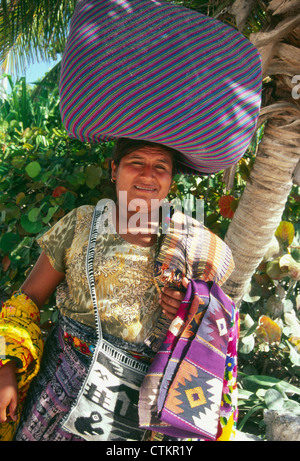 A woman selling local crafts on the beach in Belize. - Stock Photo