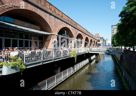 People enjoy socialising with a drink in the summer sunshine at Deansgate Locks in Manchester. - Stock Photo