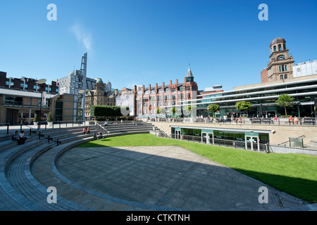 People enjoy themselves in a small amphitheatre behind Peter Street in Manchester on a sunny summer's day. - Stock Photo
