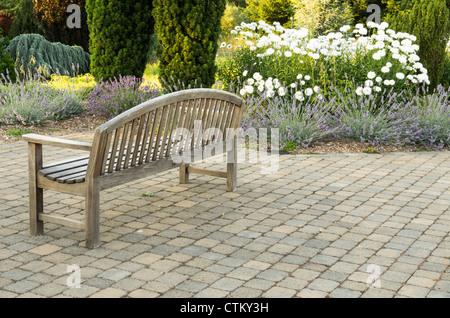 A park bench sits alone on a paved walk with white daisies in the background - Stock Photo