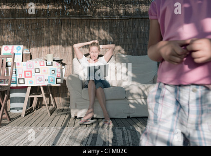 A Woman Sits On A Couch With Her Son In The Foreground; Tarifa, Cadiz, Andalusia, Spain - Stock Photo