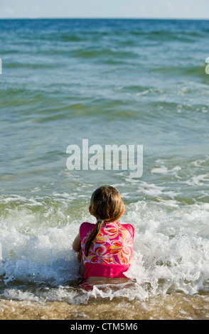 A girl sits in the sand as waves crash around her. - Stock Photo
