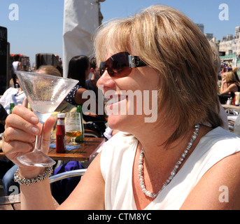Middle aged attractive blonde female enjoying a Margarita cocktail made from tequilla and lime juice at Brighton - Stock Photo