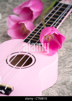 Still life with pink ukulele and pink tulips - Stock Photo