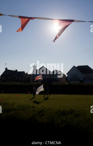 Olympic flags flying on a mini golf putting green in the Suffolk seaside town of Southwold, Suffolk. - Stock Photo
