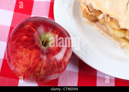 A ripe red apple on gingham tablecloth beside a slice of apple pie. - Stock Photo