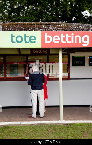 People betting on the horses at Tote betting on race night, Newmarket Racecourse Suffolk UK - Stock Photo