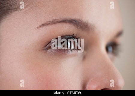 Close-up of a young woman with brown eyes, side view - Stock Photo