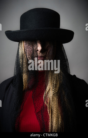 A young blonde haired girl woman wearing a hat with black victorian mourning lace covering her face - Stock Photo