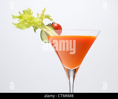 A orange vegetable juice in a stemmed glass with vegetable garnish. Celery stalk, cucumber slice and cherry tomato. - Stock Photo