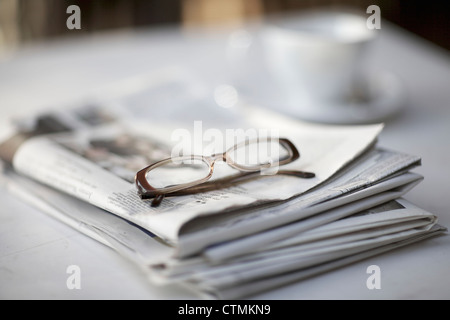 A pair of reading glasses sitting on top of a newspaper, Johannesburg, Gauteng, South Africa - Stock Photo
