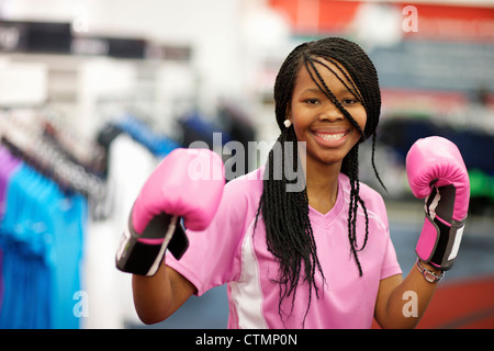 A young woman wearing boxing gloves and looking at the camera, Pietermaritzburg, KwaZulu-Natal, South Africa - Stock Photo