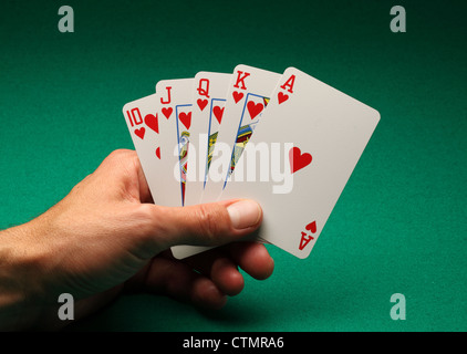 A man's hand holding playing cards on a green table. A Royal Flush in hearts in the game of Poker - Stock Photo