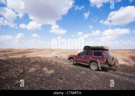 Four-Wheel drive on volcanic rocks in desert, Loyongalani region, Lake Turkana, Kenya - Stock Photo