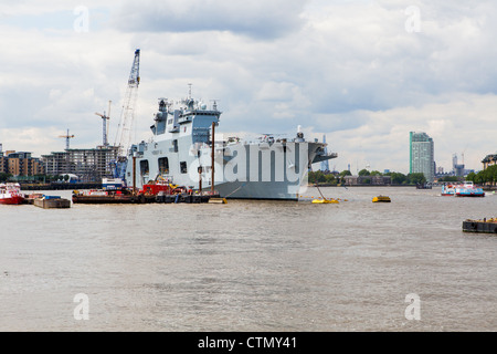 HMS Ocean moored in Greenwich with the City of London behind her - Stock Photo