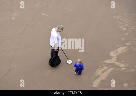 man searching beach with a metal detector, Whitby, North Yorkshire, England, UK - Stock Photo