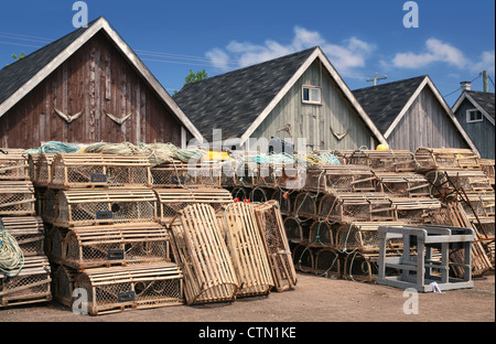 Bait sheds on a North Rustico wharf in Prince Edward Island, Canada. Lobster traps and buoys are stacked in front. - Stock Photo