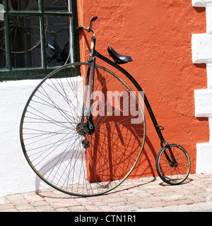 An antique bicycle leaning up against the stucco wall of a building in Bermuda. - Stock Photo
