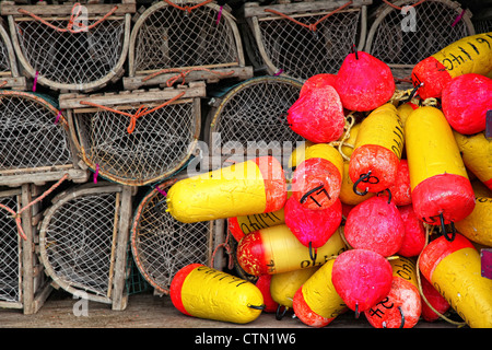 A pile of commercial lobster traps and brightly colored buoys on a wharf on Prince Edward Island, Canada. - Stock Photo