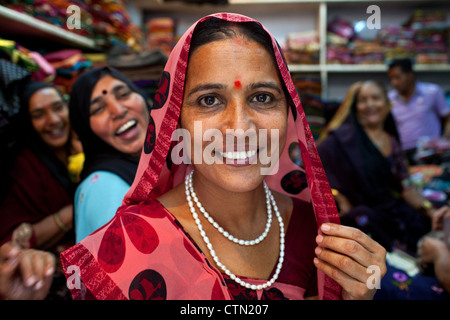 A portrait of smiling pretty Rabari women wearing traditional sari clothes in a textile shop in Ahmedabad, Gujarat - Stock Photo